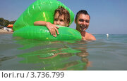 Купить «Отец и дочь в надувном круге на волнах», видеоролик № 3736799, снято 21 мая 2011 г. (c) Losevsky Pavel / Фотобанк Лори