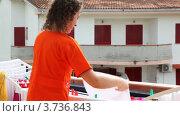 Купить «Девушка вешает выстиранную одежду сушить на балконе», видеоролик № 3736843, снято 16 июня 2011 г. (c) Losevsky Pavel / Фотобанк Лори