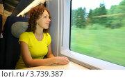 Купить «Молодая женщина сидит в поезде и смотрит в окно, улыбаясь», видеоролик № 3739387, снято 12 января 2007 г. (c) Losevsky Pavel / Фотобанк Лори
