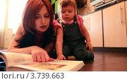 Купить «Мама и маленькая девочка лежат на полу, разглядывая книгу», видеоролик № 3739663, снято 1 мая 2011 г. (c) Losevsky Pavel / Фотобанк Лори