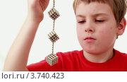Купить «Мальчик раскручивает цепь соединенных в кубы магнитных шариков», видеоролик № 3740423, снято 15 августа 2011 г. (c) Losevsky Pavel / Фотобанк Лори