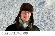 Купить «Молодой человек в ушанке улыбается на фоне снега», видеоролик № 3740799, снято 1 мая 2011 г. (c) Losevsky Pavel / Фотобанк Лори