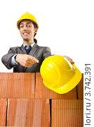 Купить «Строитель за кирпичной стеной показывает на защитный шлем», фото № 3742391, снято 22 мая 2012 г. (c) Elnur / Фотобанк Лори