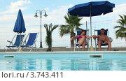 Купить «Пара сидит в шезлонгах у бассейна», видеоролик № 3743411, снято 14 мая 2011 г. (c) Losevsky Pavel / Фотобанк Лори