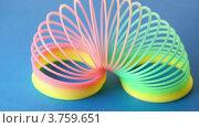 Купить «Цветная пластиковая игрушка - пружина слинки вращается, на синем фоне», видеоролик № 3759651, снято 11 октября 2011 г. (c) Losevsky Pavel / Фотобанк Лори