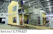 Купить «Строители возводят дом для выставки в ангаре», видеоролик № 3774827, снято 31 января 2012 г. (c) Losevsky Pavel / Фотобанк Лори