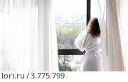 Купить «Женщина в банном халате подходит к окну, раздвигает шторы и смотрит на улицу», видеоролик № 3775799, снято 11 марта 2012 г. (c) Losevsky Pavel / Фотобанк Лори