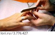 Купить «Косметолог делает маникюр и пилит ногти клиента пилкой для ногтей», видеоролик № 3776427, снято 7 февраля 2012 г. (c) Losevsky Pavel / Фотобанк Лори