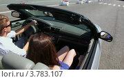 Купить «Молодой человек и девушка едут  в кабриолете по городу и улыбаются летним днем», видеоролик № 3783107, снято 30 апреля 2012 г. (c) Losevsky Pavel / Фотобанк Лори