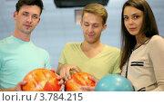 Купить «Два юноши и девушка с шарами для боулинга», видеоролик № 3784215, снято 3 мая 2012 г. (c) Losevsky Pavel / Фотобанк Лори