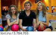 Купить «Две девушки и парень разговаривают и улыбаются в темном боулинг клубе», видеоролик № 3784703, снято 22 марта 2012 г. (c) Losevsky Pavel / Фотобанк Лори