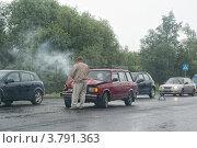 Купить «Водитель осматривает повреждения попавшего в дтп на мокром шоссе автомобиля ВАЗ», эксклюзивное фото № 3791363, снято 29 августа 2012 г. (c) Сайганов Александр / Фотобанк Лори