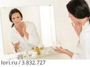 Купить «Брюнетка в белом халате наносит крем на лицо в ванной комнате, глядя в зеркало», фото № 3832727, снято 31 мая 2012 г. (c) CandyBox Images / Фотобанк Лори