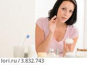 Симпатичная брюнетка наносит крем на лицо в ванной. Стоковое фото, фотограф CandyBox Images / Фотобанк Лори
