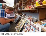 Купить «Турист выбирает сувениры магнитики», эксклюзивное фото № 3840159, снято 1 августа 2012 г. (c) Яков Филимонов / Фотобанк Лори