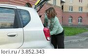 Девушка кладет огнетушитель и аварийный знак в багажник автомобиля. Стоковое видео, видеограф Кекяляйнен Андрей / Фотобанк Лори