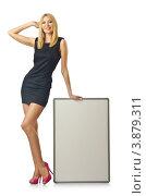 Купить «Стройная молодая женщина в коротком платье стоит рядом с баннером, изолированно на белом фоне», фото № 3879311, снято 6 июля 2012 г. (c) Elnur / Фотобанк Лори