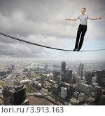 Купить «Деловая женщина балансирует на канате над современным городом», фото № 3913163, снято 18 августа 2012 г. (c) Sergey Nivens / Фотобанк Лори