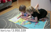 Купить «Четырехлетние девочки увлеченно рассматривают детский атлас мира на полу», видеоролик № 3950339, снято 21 октября 2012 г. (c) Кекяляйнен Андрей / Фотобанк Лори