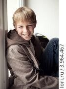 Веселый подросток сидит у окна. Стоковое фото, фотограф Римма Зайцева / Фотобанк Лори