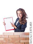 Купить «Девушка в вьющимися волосами стоит у кирпичной кладки и показывает на планшет с пустым листом бумаги», фото № 3973451, снято 27 июля 2012 г. (c) Elnur / Фотобанк Лори