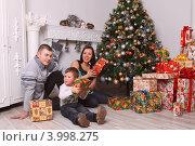 Семья- папа, мама и мальчик четырех  лет на Новый год и рождество у елки с подарками и часами. Стоковое фото, фотограф Вероника Горбова / Фотобанк Лори