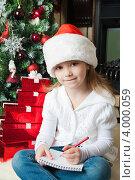 Купить «Симпатичная девочка сидит около елки и пишет письмо Деду морозу», фото № 4000059, снято 4 ноября 2012 г. (c) Оксана Гильман / Фотобанк Лори