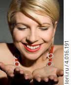 Молодая женщина смотрит на раскрытые пустые ладони и улыбается. Стоковое фото, фотограф Syda Productions / Фотобанк Лори
