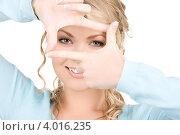 Купить «Привлекательная девушка в голубом джемпере на белом фоне показывает рамку на пальцах», фото № 4016235, снято 26 сентября 2009 г. (c) Syda Productions / Фотобанк Лори