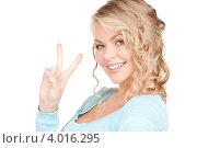 Купить «Привлекательная девушка в голубом джемпере на белом фоне показывает на пальцах знак победы», фото № 4016295, снято 26 сентября 2009 г. (c) Syda Productions / Фотобанк Лори