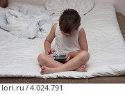 Купить «Мальчик в нижнем белье сидящий на разобранной кровати играет в игры на смартфоне», эксклюзивное фото № 4024791, снято 15 июля 2012 г. (c) Родион Власов / Фотобанк Лори