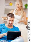Купить «Молодой человек сидит с планшетным компьютером в руках на диване, недовольная девушка рядом», фото № 4044939, снято 4 августа 2012 г. (c) Syda Productions / Фотобанк Лори