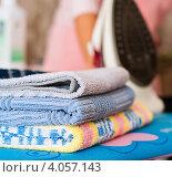 Купить «Глаженные полотенца лежат на доске на фоне утюга», эксклюзивное фото № 4057143, снято 21 сентября 2012 г. (c) Игорь Низов / Фотобанк Лори