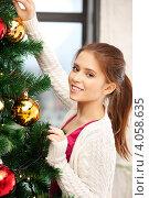 Купить «Привлекательная юная девушка наряжает новогоднюю ель дома», фото № 4058635, снято 13 ноября 2011 г. (c) Syda Productions / Фотобанк Лори