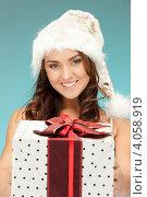 Купить «Симпатичная молодая женщина в колпаке Санты-Клауса, короткой юбке и длинными волосами с подарком в руках», фото № 4058919, снято 22 ноября 2011 г. (c) Syda Productions / Фотобанк Лори