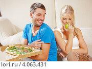 Купить «Девушка грызет зеленое яблоко, а молодой человек ест вредную пиццу на фоне дивана дома», фото № 4063431, снято 4 августа 2012 г. (c) Syda Productions / Фотобанк Лори