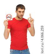 """Купить «Молодой человек в красной футболке с карточкой со знаком """"Не курить"""" в руке на белом фоне», фото № 4066259, снято 7 октября 2012 г. (c) Syda Productions / Фотобанк Лори"""