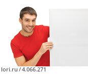 Купить «Молодой человек в красной футболке с чистым билбордом в руках», фото № 4066271, снято 7 октября 2012 г. (c) Syda Productions / Фотобанк Лори