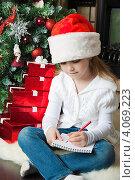 Купить «Девочка в новогоднем колпаке сидит около елки и пишет письмо Деду Морозу», фото № 4069223, снято 4 ноября 2012 г. (c) Оксана Гильман / Фотобанк Лори