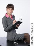Купить «Деловая девушка делает запись в своем блокноте сидя на столе», фото № 4073915, снято 1 декабря 2012 г. (c) Михаил Иванов / Фотобанк Лори