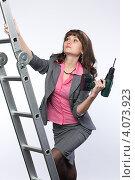 Купить «Девушка в деловом костюме с электро дрелью в руке», фото № 4073923, снято 1 декабря 2012 г. (c) Михаил Иванов / Фотобанк Лори