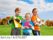 Купить «Счастливые дети с книжками стоят на зелёной траве в парке», фото № 4074887, снято 29 сентября 2012 г. (c) Сергей Новиков / Фотобанк Лори