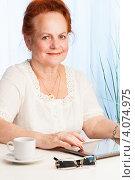 Пожилая женщина за столом с планшетным компьютером и чашечкой кофе. Стоковое фото, фотограф Сергей Новиков / Фотобанк Лори