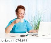 Пожилая женщина завтракает за ноутбуком. Стоковое фото, фотограф Сергей Новиков / Фотобанк Лори