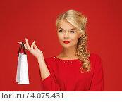 Купить «Привлекательная блондинка с покупкой в руках на красном фоне», фото № 4075431, снято 7 октября 2012 г. (c) Syda Productions / Фотобанк Лори