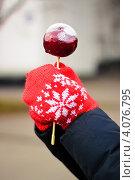 Руки в красных вязаных рукавицах держат леденец на палочке. Стоковое фото, фотограф Ксения Доброскок / Фотобанк Лори