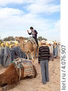 Экскурсовод показывает туристам как правильно сидеть на верблюде. Douz, Tunisia (2012 год). Редакционное фото, фотограф Кекяляйнен Андрей / Фотобанк Лори
