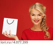 Купить «Очаровательная блондинка в красном платье с покупкой в бумажном пакете в руке на красном фоне», фото № 4077399, снято 7 октября 2012 г. (c) Syda Productions / Фотобанк Лори