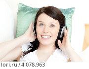 Купить «Девушка улыбается и слушает музыку в наушниках, лёжа на диване», фото № 4078963, снято 31 марта 2010 г. (c) Wavebreak Media / Фотобанк Лори