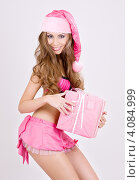 Купить «Привлекательная сексуальная девушка в колпаке Санта-Клауса с подарком, перевязанным лентой, в руках», фото № 4084999, снято 20 сентября 2008 г. (c) Syda Productions / Фотобанк Лори